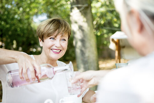 Smiling senior woman pouring water into friend's glass - WESTF22685