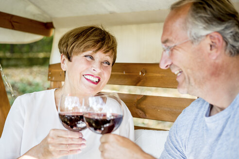 Happy senior couple clinking red wine glasses - WESTF22694