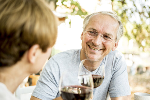 Smiling senior couple clinking red wine glasses outdoors - WESTF22697