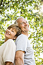 Portrait of happy senior couple back to back outdoors - WESTF22712