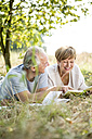 Happy senior couple with book lying in meadow - WESTF22721