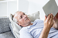 Mature man at home lying on couch using digital tablet - WESTF22727