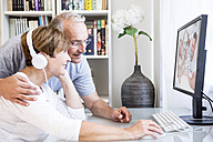 Senior couple at desk having a video conference with their family - WESTF22736