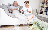 Happy senior couple at home sitting on couch drinking coffee - WESTF22742