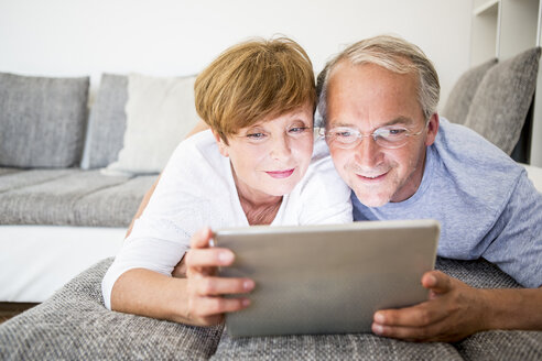 Senior couple at home lying on couch using digital tablet - WESTF22751