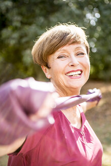 Portrait of smiling senior woman exercising with resistance band outdoors - WESTF22763