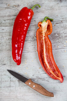 Whole and sliced red pointed pepper and a kitchen knife on wood - JUNF00836