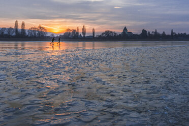 Germany, two ice skaters on frozen Lake Constance with Reichenau Island in the background at sunset - KEBF00472