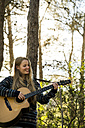 Happy young woman playing guitar in nature - KKAF00413