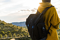 Young woman with backpack in nature at sunset - KKAF00422
