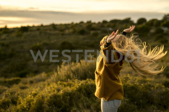 Young woman standing in nature raising her arms - KKAF00425