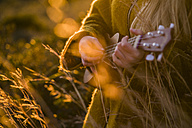 Close-up of woman playing ukulele in nature - KKAF00437