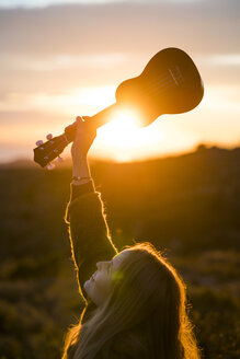 Young woman holding up ukulele in nature - KKAF00440