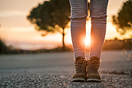 Woman wearing hiking boots standing on a road at sunset - KKAF00443