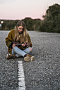 Young woman playing ukulele on a road - KKAF00446