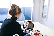 Woman on bed using laptop - VABF01113