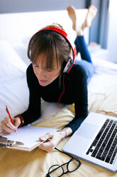 Young woman lying on bed writing on clipboard - VABF01128