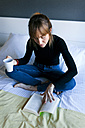 Young woman sitting on bed drinking cup of coffee and reading a book - VABF01134