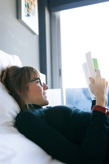 Young woman lying on bed reading a book - VABF01137