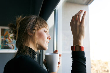 Young woman drinking cup of coffee looking out of window - VABF01140