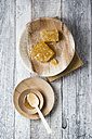 Honeycombs and honey on wooden plates - MYF01869