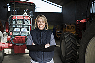 Woman standing with arms crossed in front of tractor in farm garage - JASF01528