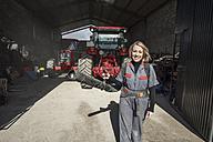 Woman in farm garage carrying air blower - JASF01546