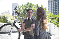 Young woman talking to young man, carrying bicycle on his shoulder - ZEF12838