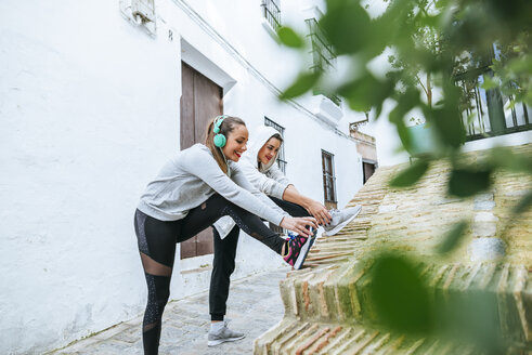 Two young women dong stretching exercises in the street - KIJF01230