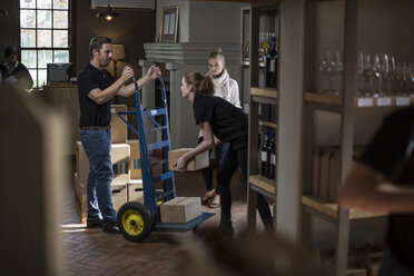 Wine staff with hand truck with boxes of wine stock in wine shop - ZEF12856