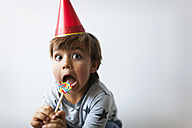 Portrait of little boy with lollipop and red party hat pulling funny faces - VABF01146