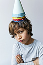 Portrait of little boy with four party hats on his head pouting mouth - VABF01152