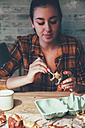 Young woman painting bear plastic figure with gold paint - RTBF00670