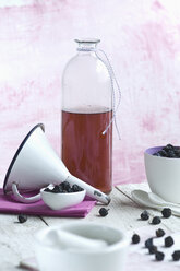 Glass bottle of homemade sloe sirup, funnel and fruits - ASF06067