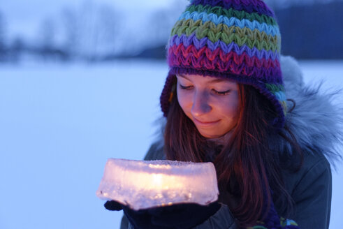 Smiling teenage girl holding cake made of ice with candle inside - LBF01567