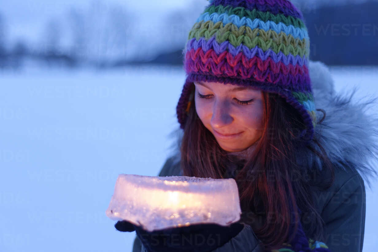 Smiling teenage girl holding cake made of ice with candle inside - LBF01567 - Lisa und Wilfried Bahnmüller/Westend61