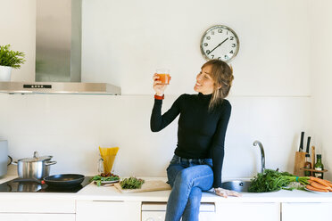 Young woman drinking fresh grapefruit juice in her kitchen - VABF01163