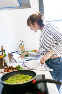Young woman cooking at home using digital tablet for recipe - VABF01169