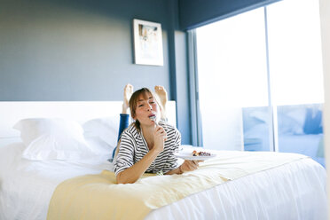 Young woman eating piece of vegan cake, lying on bed, licking spoon - VABF01199