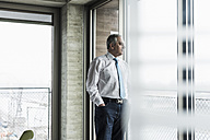 Senior manager in office standing at the window - UUF09925