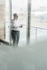 Senior manager in office standing at window, talking on the phone - UUF09955