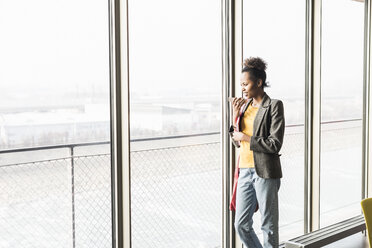 Young woman standing at window using smart phone - UUF09976