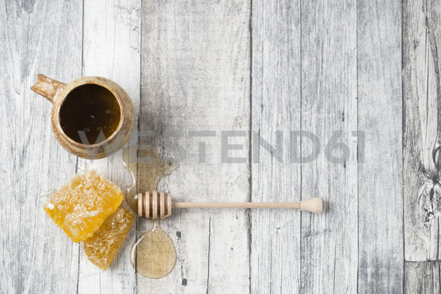 Honeycombs, clay pot and honey dipper on wood - MYF01873