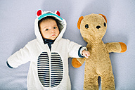 Newborn baby girl on bed wearing a bear suit next to a teddy bear - GEMF01475