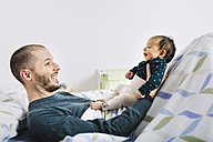 Happy father lying playing with his newborn baby girl in bed - GEMF01478