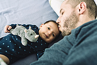 Father kissing his newborn baby girl on bed - GEMF01484