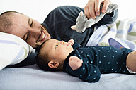 Father playing with his newborn baby girl and a a cuddly toy on bed - GEMF01487