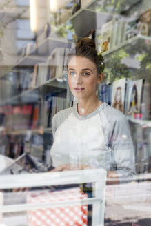 Young woman in a bookshop looking through window - LMF00613