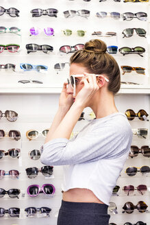 Young woman putting on sunglasses in an optician shop - LMF00619