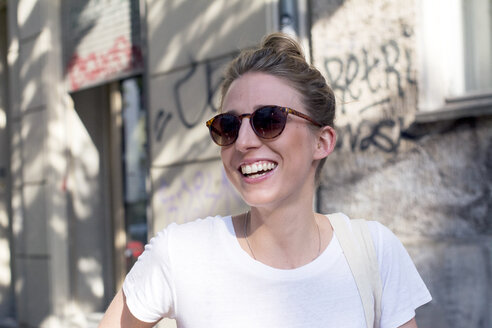 Portrait of laughing young woman wearing sunglasses - LMF00628
